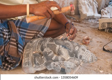 MAHABALIPURAM, TAMIL NADU, INDIA, 01 DECEMBER  2018 : Unidentified man carving stone statue with hammer in his street shop at Mahabalipuram, This type of craft is very popular in India.