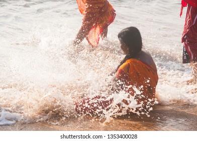 MAHABALIPURAM, TAMIL NADU, INDIA 02 DECEMBER 2017 : Unidentified women Tourist in red saree and enjoying on the Beach of Indian ocean at sunrise.