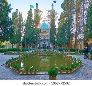 MAHAN, IRAN - OCTOBER 16, 2017: The scenic Vakil-ol-Molki courtyard of Shah Nematollah Vali Shrine with coniferous garden, polygonal pond and turquoise tiled patterns on dome, on October 16 in Mahan.