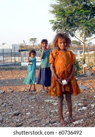 MAHARASHTRA, INDIA - CIRCA 2008: Unidentified children collect cotton blown outside the perimeter of a cotton factory circa 2008 in India. They often sell the cotton back to the processing factory.