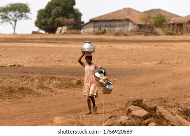 Maharashtra, India/May 29, 2018: A young girl carry stainless containers to fetch water from a nearly dry well at Mal village, Shahapur Taluka, Thane District.