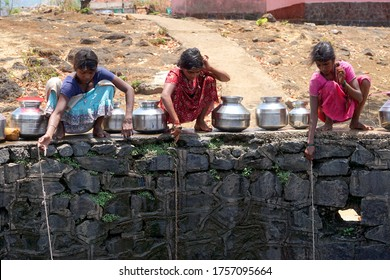 Maharashtra, India/May 6, 2016: Children fetch water from a nearly dry well at Dhakne village, Shahapur Taluka, Thane District.