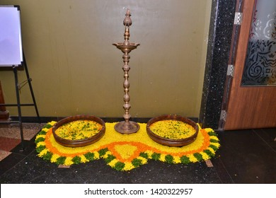 Maharashtrian Wedding - Flower Rangoli decoration with traditional lamp (Samai) to welcome relatives made using Marigold or Zendu flowers and green petals over black tiles background