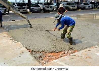 MAHASARAKHAM - OCTOBER 8 : Masonry workers repair concrete parking floor at Sermthai complex on October 8, 2014 in Mahasarakham, Thailand.