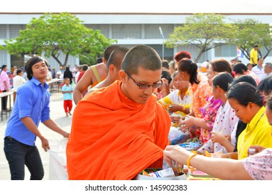 MAHASARAKHAM, THAILAND - APRIL 13 : Unidentified people are giving food offering to monks in Thai New Year Festival on April 13, 2013 in City Hall Plaza, Payakkaphumphisai, Mahasarakham, Thailand.