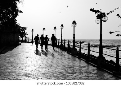 Mahe, Puducherry, India - January, 2017: Silhouettes of four men walking on the seafront park with paved walkway and street lights.