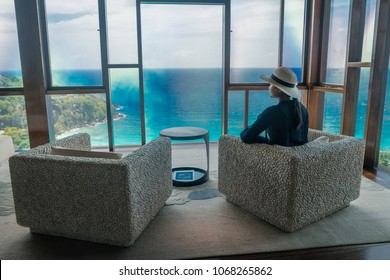 Mahe Seychelles March 2018,  woman in an chair lookin out over the ocean at the luxury Four Seasons resort