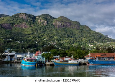 Mahe, Seychelles - Oct 26th 2018 - Fisherman boats in the Mahe's port in Seychelles with mountains covered with green vegetation in the background