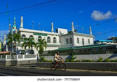 Mahebourg, Mauritius - Jan 9, 2017. A man biking on street at sunny day in Mahebourg, Mauritius. Mauritius is a major tourist destination, ranking 3rd in the region.