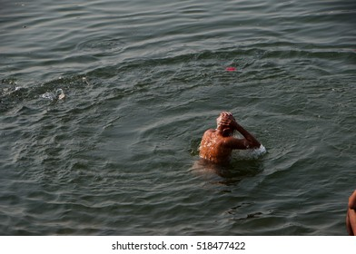 MAHESWAR, MADHYA PRADESH, INDIA, 17 OCTOBER 2011 : Unidentified people washing themselves and performs morning pooja on sacred river Narmada in front of Maheshwar palace.