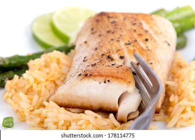 mahi mahi fish fillet on rice with asparagus