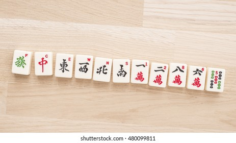 Mahjong board game pieces lying on wood table from above. Concept of asian or chinese leisure activity, recreation and traditional games.