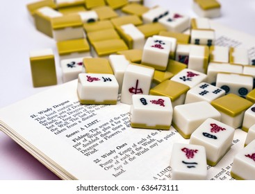 Mahjong Tiles; jumbled group of mahjong tiles resting on rule-book; differential focus;