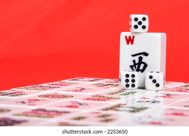 Mahjong wind tile and dice sitting on top of mahjong playing