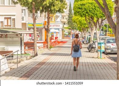 Mahmutlar, Antalya Province, Turkey / 05-22-2019: Tourist woman walks on the street of Turkish resort shore town.