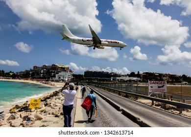 MAHO BAY BEACH, SINT MAARTEN - AUGUST 1, 2015: Aeroplane Caribbean Airlines is landing on Princess Juliana International Airport, over Maho Bay Beach seen in St.Martin/St.Maarten.
