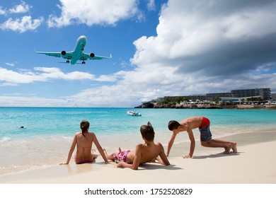 Maho Beach, Princess Juliana Airport, St. Maarten (Saint-Martin) / Antilles - 02.29.2020. Children on the beach playing in the sand under a low flying Boeing 767 aircraft of American Airlines.
