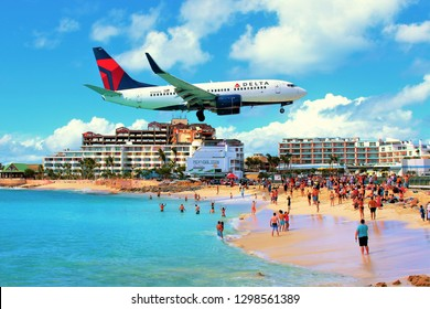 Maho Beach, Sint Maarten, Caribbean - February 27th 2018: A Delta Air Lines plane flying low over the famous Maho beach as it comes in to land at Princess Juliana International Airport.