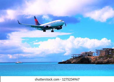 MAHO, ST MAARTEN, CARIBBEAN - FEBRUARY 27TH 2018: A shot from Maho beach of a Delta Air Lines passenger plane coming in to land at SXM Princess Juliana Airport behind.