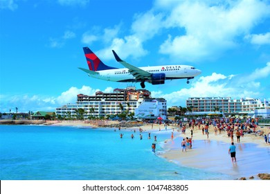 MAHO, ST MAARTEN - FEBRUARY 27TH 2018: A Delta Air Lines passenger jet flying over Maho bay as it comes in to land at SXM Princess Juliana International Airport behind.