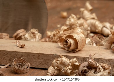 Mahogany wood block and wood shavings. Carpenter cabinet maker hand tools on the workbench.