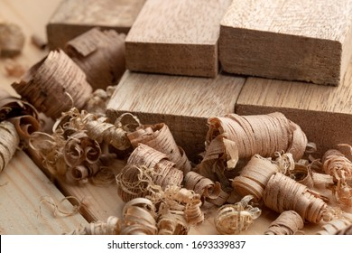 Mahogany wood block and wood shavings. Wood shavings of different sizes from woodworking.