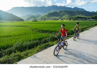 Mai Chau, Vietnam - August 7, 2019: Two kids playing and riding bicycles among rice fields, in the Mai Chau valley, Vietnam