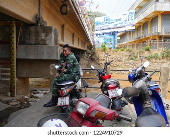 MAI SAI, THAILAND—MARCH 2018: A border guard sits on a motorcycle beside Sai River bordering Thailand and Myanmar.