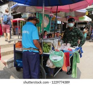 MAI SAI, THAILAND—MARCH 2018: A border guard stands by a fruit stall in Mai Sai near the Thai-Burmese gate.