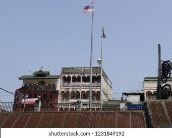 MAI SAI, THAILAND—MARCH 2018: Building with a flag flying across River Sai bordering Thailand and Myanmar.