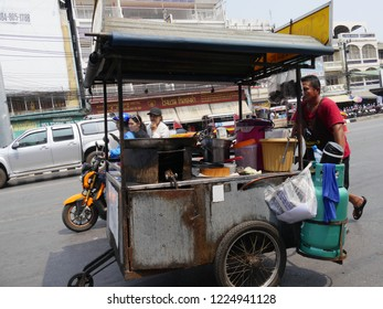 MAI SAI, THAILAND—MARCH 2018: Close up of a man pushing his food cart across the street in Mai Sai, the last city bordering Thailand and Myanmar.