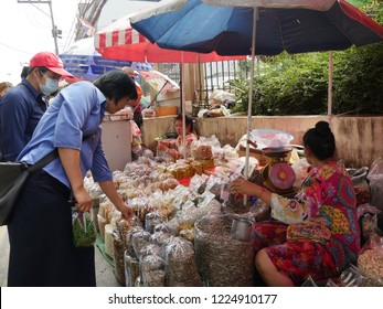 MAI SAI, THAILAND—MARCH 2018: Customers buy assorted nuts and Thai delicacies in Mai Sai, the last city bordering Thailand and Myanmar.