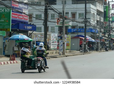 MAI SAI, THAILAND—MARCH 2018: A delivery crew rides on a motorized sidecar in Mai Sai, the last city bordering Thailand and Myanmar.