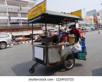 MAI SAI, THAILAND—MARCH 2018: A man pushes his food cart across the street in Mai Sai, the last city bordering Thailand and Myanmar.