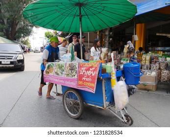 MAI SAI, THAILAND—MARCH 2018: A man pushings his food cart along the street in Mai Sai, the last city bordering Thailand and Myanmar.