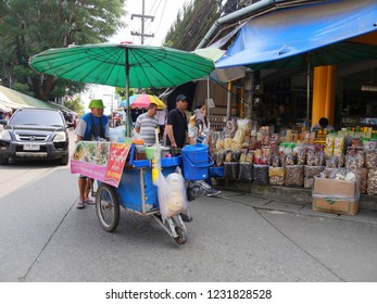 MAI SAI, THAILAND—MARCH 2018: A man selling fresh foods pushes a cart along the street in Mai Sai, the last city bordering Thailand and Myanmar.
