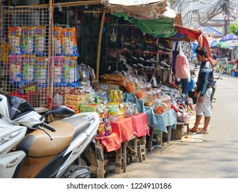 MAI SAI, THAILAND—MARCH 2018: A man stands outside a stall displa of delicacies and other merchandise at Mai Sai bordering Thailand and Myanmar.