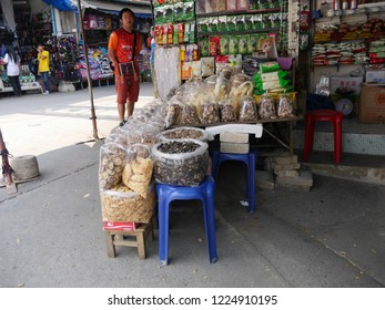 MAI SAI, THAILAND—MARCH 2018: A man stands beside stall display of assorted Thai delicacies in Mai Sai bordering Thailand and Myanmar.