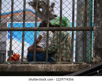 MAI SAI, THAILAND—MARCH 2018: Medium wide shot of a woman and child sits on the roadside behind bars at the Sai River bridge bordering Thailand and Myanmar.