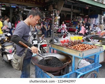 MAI SAI, THAILAND—MARCH 2018: A sidewalk vendor roasts nuts in his cart along the road in Mai Sai, the last city bordering Thailand and Myanmar.