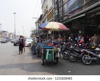 MAI SAI, THAILAND—MARCH 2018: Sidewalk vendors line up along the road in Mai Sai, the last city bordering Thailand and Myanmar.