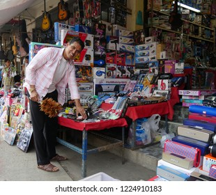 MAI SAI, THAILAND—MARCH 2018: A storeowner dusts his displays of electronics and assorted goods at Mai Sai bordering Thailand and Myanmar.