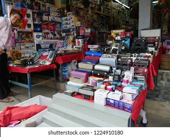 MAI SAI, THAILAND—MARCH 2018: A storeowner stands beside his displays of electronics and assorted goods at Mai Sai bordering Thailand and Myanmar.