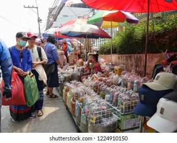 MAI SAI, THAILAND—MARCH 2018: Tourists check out the assorted displays of  nuts and Thai delicacies in Mai Sai, the last city bordering Thailand and Myanmar.