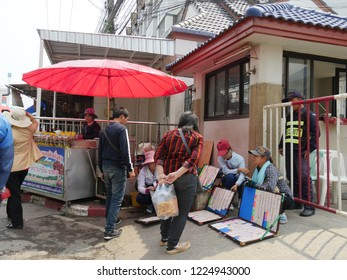 MAI SAI, THAILAND—MARCH 2018: Tourists check out displays of lottery tickets sold on the streetside of Mai Sai, the last city bordering Thailand and Myanmar.