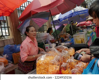 MAI SAI, THAILAND—MARCH 2018: A woman buys delicacies from a roadside stall in Mai Sai, the last city bordering Thailand and Myanmar.