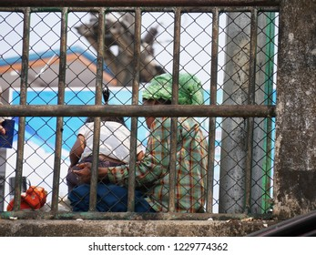 MAI SAI, THAILAND—MARCH 2018: A woman and child sits on the roadside behind bars at the Sai River bridge bordering Thailand and Myanmar.
