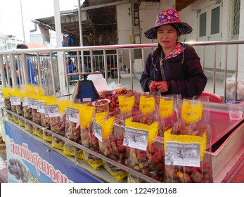 MAI SAI, THAILAND—MARCH 2018: A woman displays assorted fruit by the roadside in Mai Sai, the last city bordering Thailand and Myanmar.
