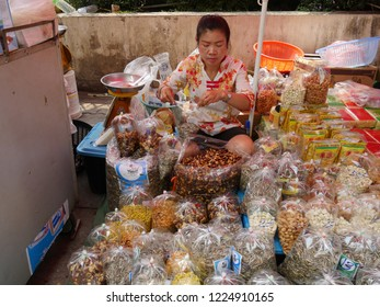 MAI SAI, THAILAND—MARCH 2018: A woman measures nuts for retail at her stall in Mai Sai, the last city bordering Thailand and Myanmar.