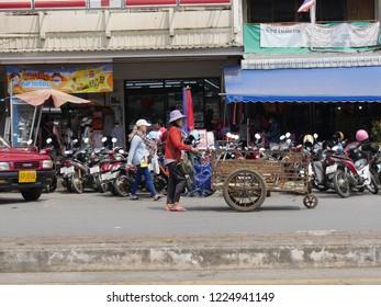 MAI SAI, THAILAND—MARCH 2018: A woman pushes an empty cart along the sidewalk in Mai Sai, the last city bordering Thailand and Myanmar.